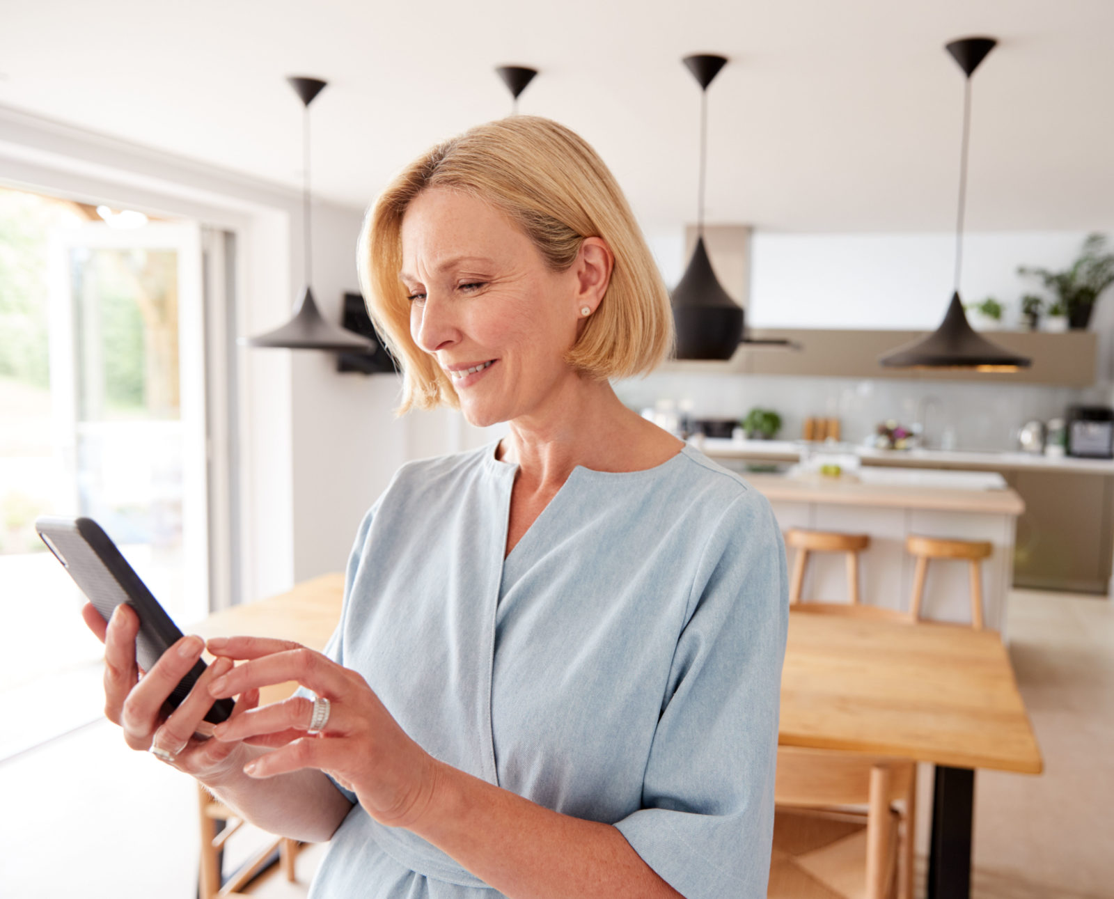 Mature,Woman,Using,App,On,Mobile,Phone,To,Control Temperature In House
